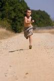 男孩多灰尘的路运行中 图库摄影