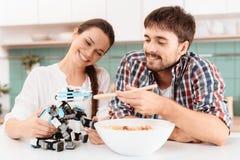 男孩夫妇果子女孩厨房使打孔机尝试新 人和女孩哺养小的犀牛机器人 免版税图库摄影