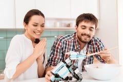 男孩夫妇果子女孩厨房使打孔机尝试新 人和女孩哺养小的犀牛机器人 免版税库存图片