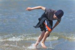 男孩奔跑通过在俄勒冈海岸的海浪 库存图片