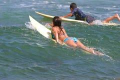 男孩女孩去夏威夷冲浪的年轻人 库存照片