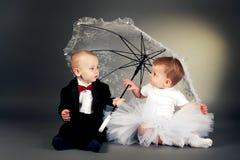 男孩女孩少许坐的伞下 免版税库存照片