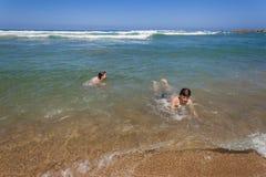 男孩女孩游泳海洋Shorebreak 库存图片
