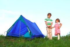 男孩女孩现有量在帐篷附近暂挂 免版税库存照片