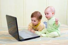 男孩女孩膝上型计算机一点使用 库存图片
