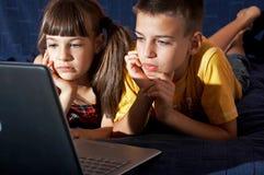 男孩女孩膝上型计算机使用 库存图片