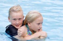 男孩女孩藏品池粗暴的人水 免版税库存照片
