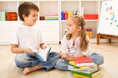 男孩她一点如何读了显示姐妹的学校 免版税库存照片