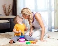 男孩她的亲吻爱恋的母亲的孩子 免版税库存图片
