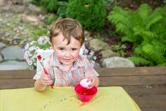 男孩姿势用他的桃红色复活节彩蛋 图库摄影