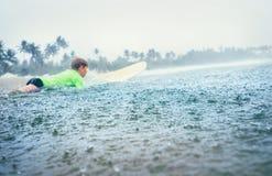 男孩学会第一步的冲浪者冲浪在热带雨下 库存图片