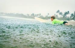 男孩学会第一步的冲浪者冲浪在热带雨下 免版税库存图片