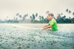 男孩学会第一步的冲浪者冲浪在雨下 免版税库存照片