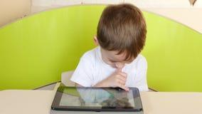 男孩孩子在桌,看和感人的手上坐电子片剂片剂,微笑 影视素材