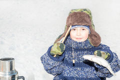 男孩孩子在渔冬天抓了在一个诱饵的一条鱼 冬季体育和滚刀 库存照片