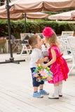 男孩孩子在生日给花和亲吻女孩孩子 库存照片