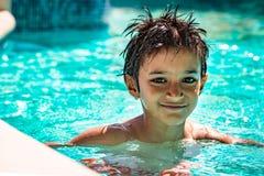 男孩孩子孩子八岁在游泳池画象愉快的乐趣明亮的天里面 免版税库存照片