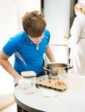 男孩孩子烘烤松饼 准备松饼的儿童中小学生在厨房里 库存图片