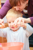 男孩孩子烘烤蛋糕。闯进鸡蛋的孩子碗。厨房。 免版税图库摄影