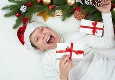 男孩孩子获得乐趣激动圣诞节装饰、面孔表示和愉快的,穿戴在圣诞老人帽子,在白色毛皮backgro说谎 免版税库存图片