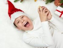 男孩孩子获得乐趣激动圣诞节装饰、面孔表示和愉快的,穿戴在圣诞老人帽子,在白色毛皮backgro说谎 免版税图库摄影