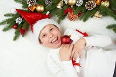 男孩孩子获得乐趣激动圣诞节装饰、面孔表示和愉快的,穿戴在圣诞老人帽子,在白色毛皮backgro说谎 库存照片