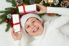 男孩孩子获得乐趣激动圣诞节装饰、面孔表示和愉快的,穿戴在圣诞老人帽子,在白色毛皮backgro说谎 库存图片