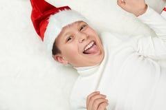 男孩孩子获得乐趣激动圣诞节装饰、面孔表示和愉快的,穿戴在圣诞老人帽子,在白色毛皮backgro说谎 图库摄影
