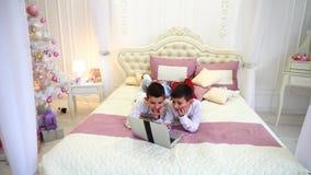 男孩孪生摆在和使用在膝上型计算机,说谎在床上在明亮的屋子里与圣诞树自白天 股票视频