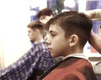 男孩安排他的头发被剪在理发店男盥洗室 免版税图库摄影