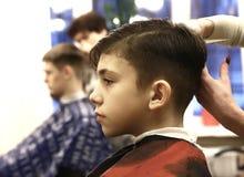 男孩安排他的头发被剪在理发店男盥洗室 库存图片