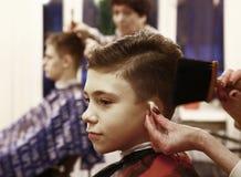 男孩安排他的头发被剪在理发店男盥洗室 免版税库存照片