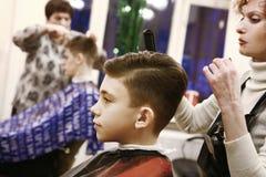 男孩安排他的头发被剪在理发店男盥洗室 免版税库存图片