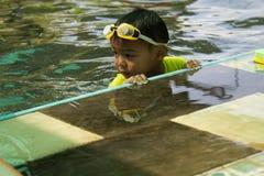 男孩实践游泳 活动子项合并游泳 免版税库存照片