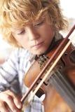 男孩实践的小提琴在家 库存图片