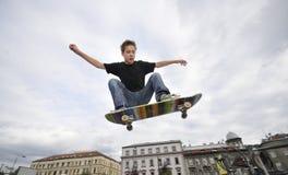 男孩实践的踩滑板 免版税图库摄影