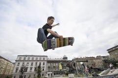 男孩实践的踩滑板 免版税库存照片