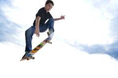 男孩实践的踩滑板 免版税库存图片