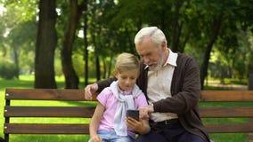 男孩对愉快的祖父,对老人的容易的申请的陈列智能手机 股票录像