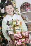 男孩对许多圣诞节礼物满意 免版税库存图片