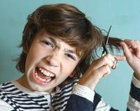 男孩对他自己的切口头发与剪刀 免版税库存图片