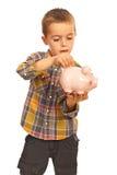男孩对piggybank的节省额货币 免版税库存图片
