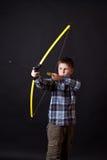 男孩射击一把弓 免版税库存图片