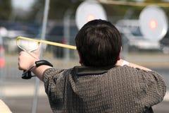 男孩射击射击吊索 免版税库存照片