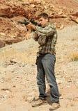 男孩射击瞄准少年 免版税库存照片