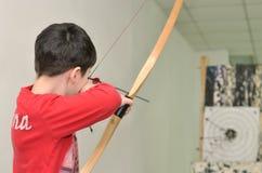 男孩射击一个箭头在目标 免版税库存图片