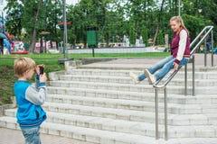 男孩射击智能手机的女孩 库存照片