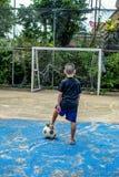 男孩将射击在沥青的橄榄球 库存照片
