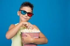 男孩小心地观看在3D玻璃的一部电影,与一个桶玉米花,戏院的概念,并且娱乐,整理 免版税库存照片