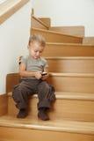 男孩小的坐的台阶 免版税库存图片